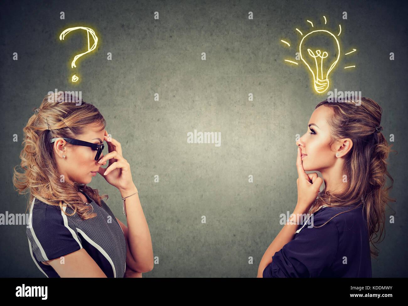 Zwei Frauen denken hat eine Frage eine andere Lösung mit Glühbirne über dem Kopf auf grauem Hintergrund. Stockbild