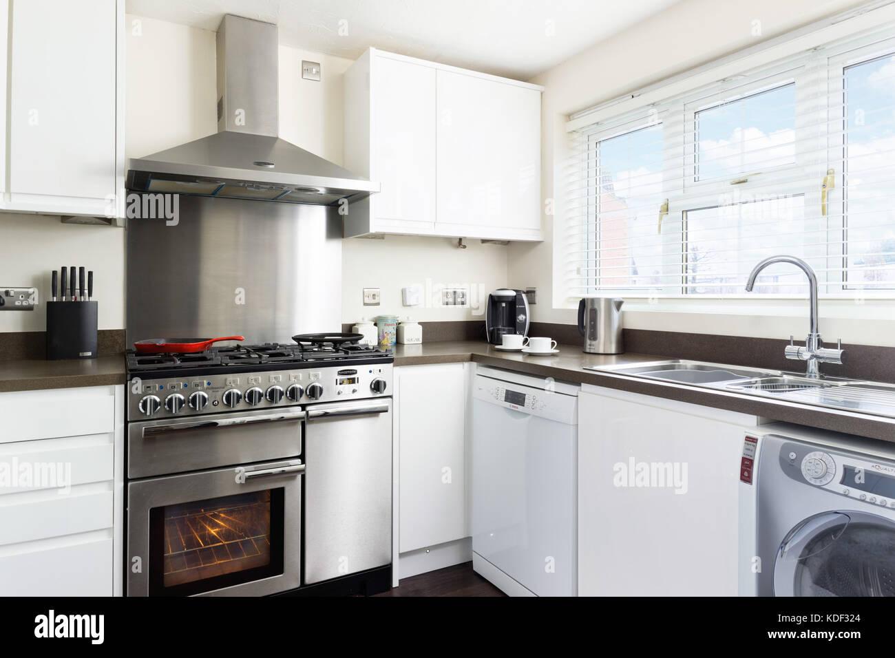 Eine kleine, saubere, frische, weiße Küche mit sortiment Edelstahl ...