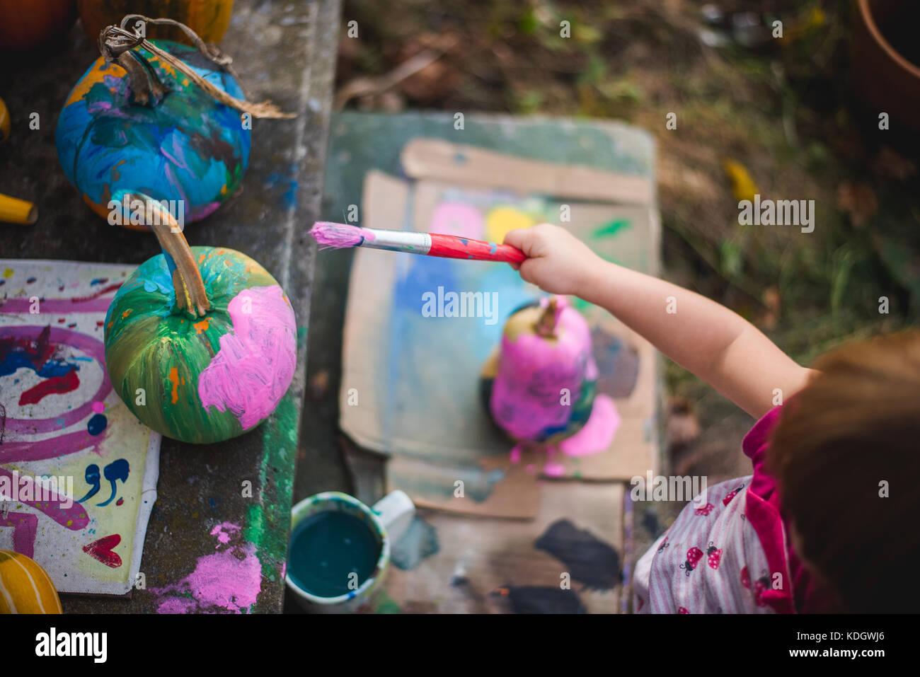 Ein kleines Mädchen malt Kürbisse im Herbst Aktivitäten. Stockbild