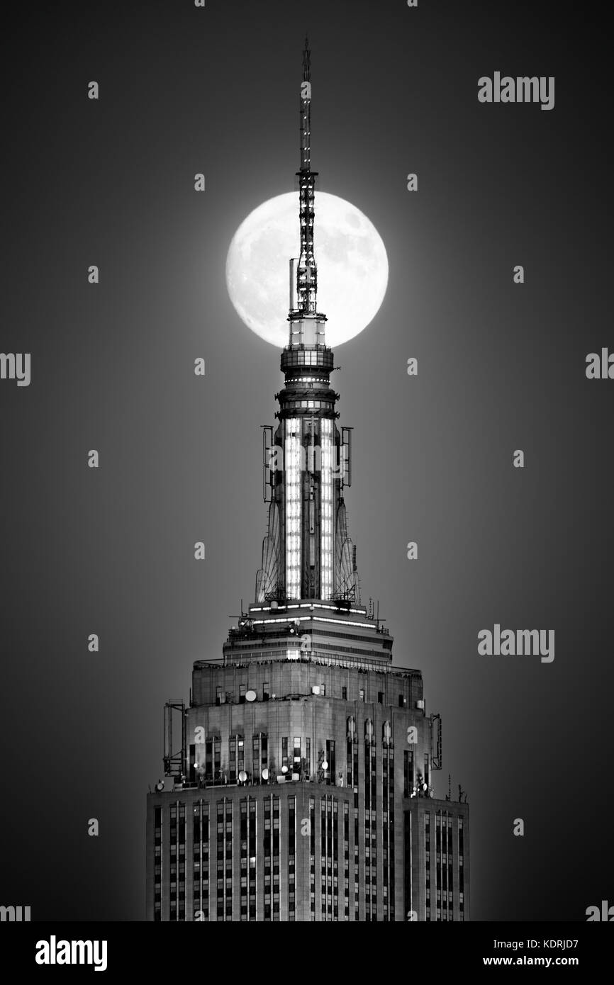 Hoboken, NJ - 13. November 2016: Vollmond steigt und richtet mit der Spitze des Empire State Building. Stockbild