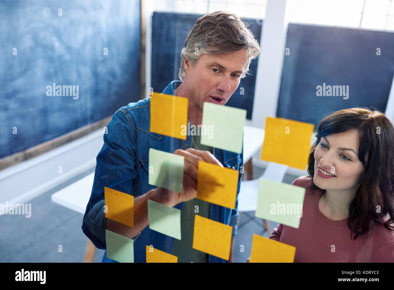 Lächelnd Mitarbeiter Brainstorming über eine Glaswand in einem Büro Stockbild