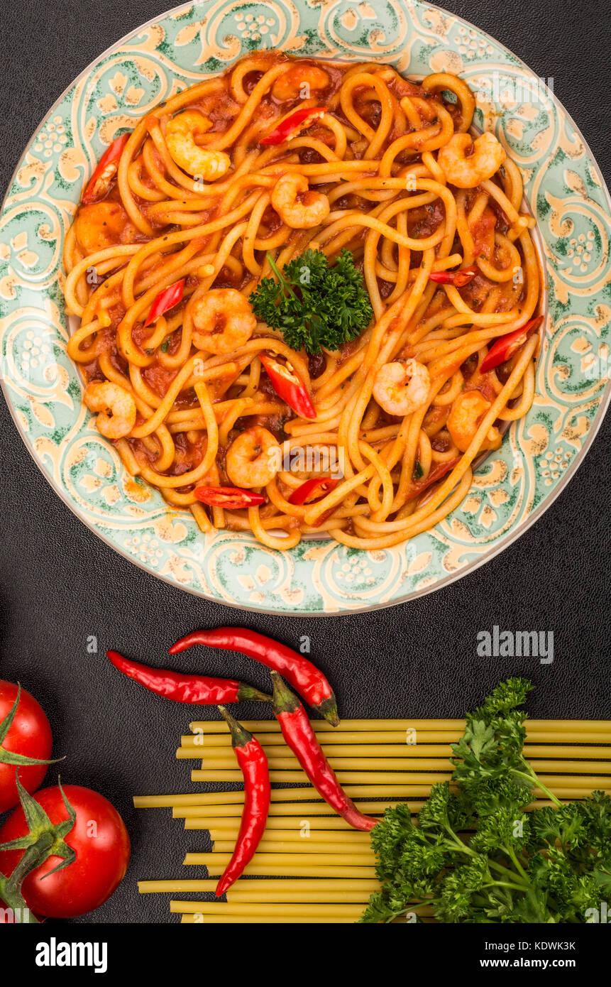 Im italienischen Stil würzige Garnelen oder Shrimps Spaghetti in einem Chili Tomatensauce auf schwarzem Hintergrund Stockbild