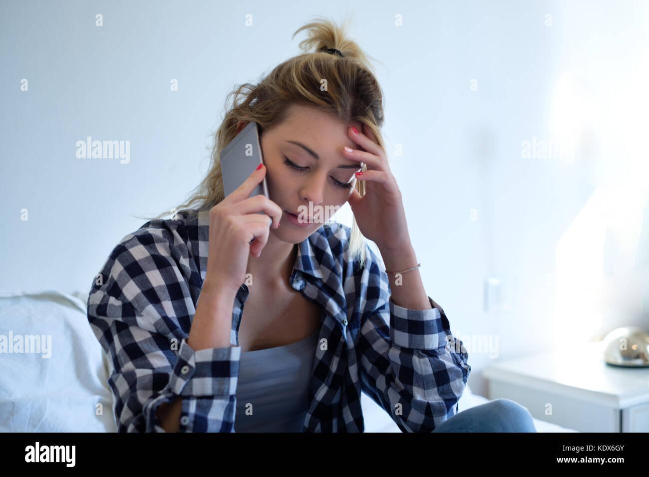 Junge traurig emotionale hübsches Mädchen auf dem Bett innen- und sprechen über das Telefon sitzt Stockbild