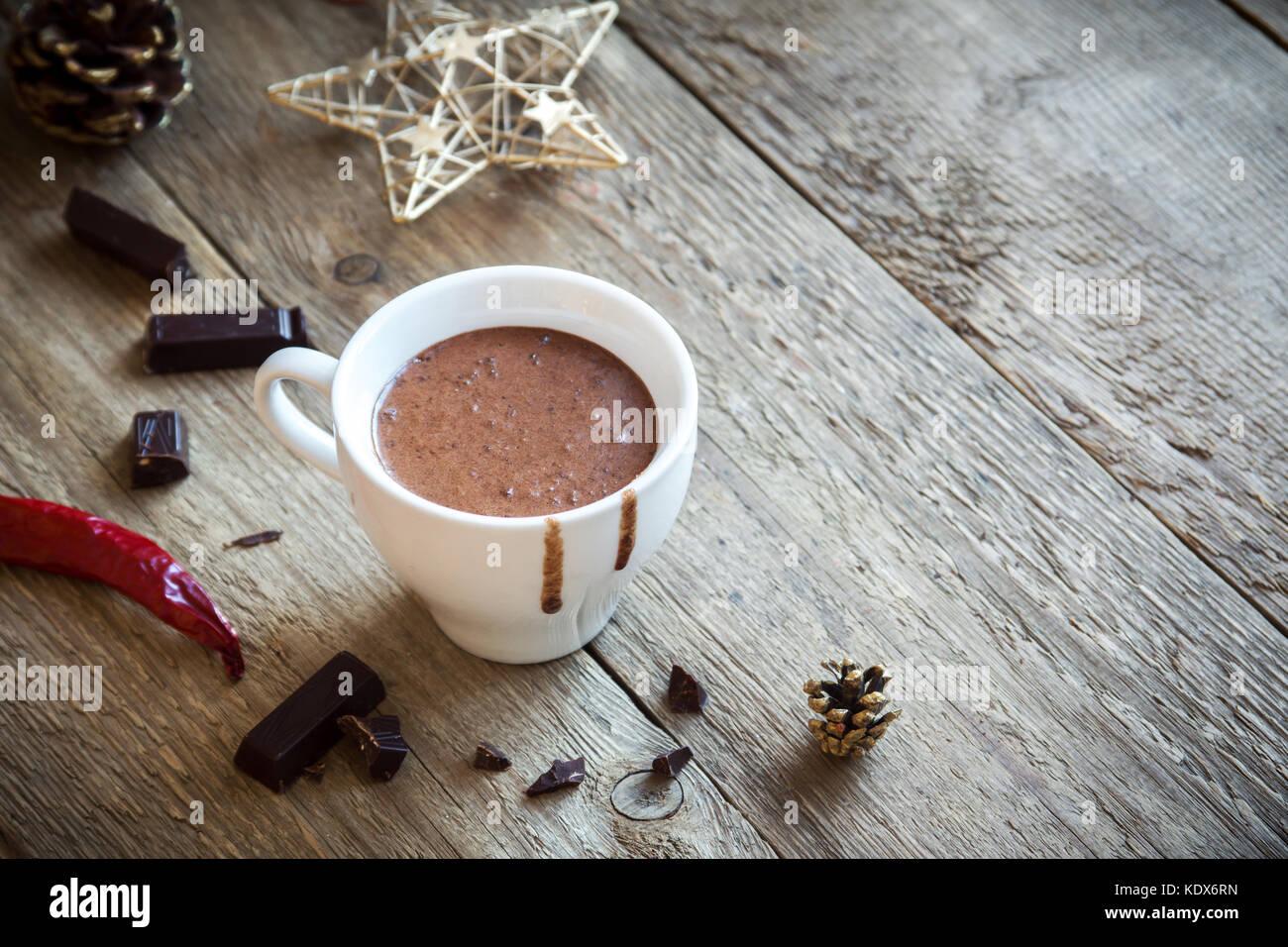 Heiße Schokolade mit Chili und Schokolade Stücke über rustikal Hintergrund. hausgemachte heiße Stockbild