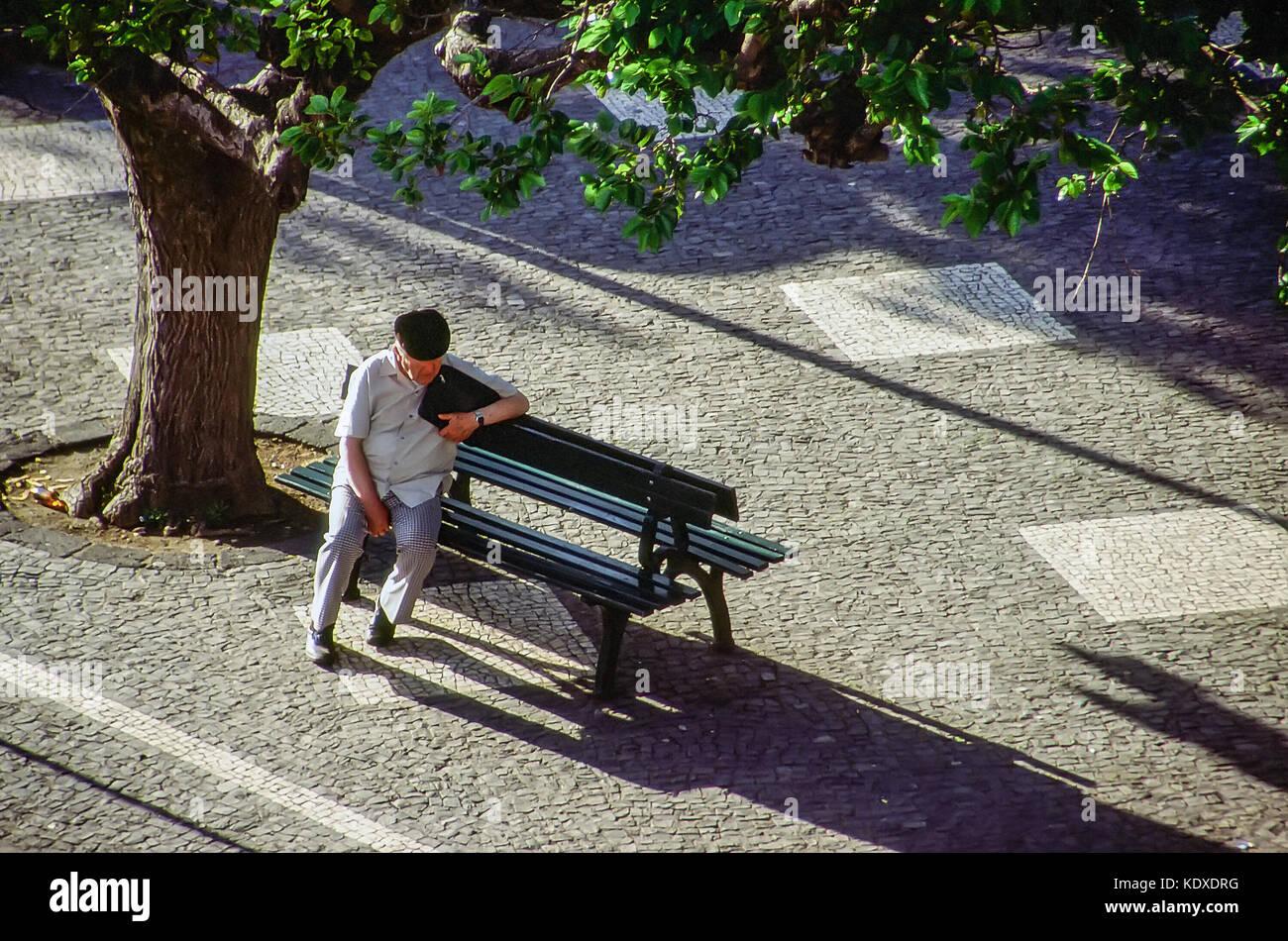 Ein älterer Mann sitzt alleine auf einer Parkbank in Angra do Hiroismo, auf der Insel Terceira, Azoren. Die Stockbild