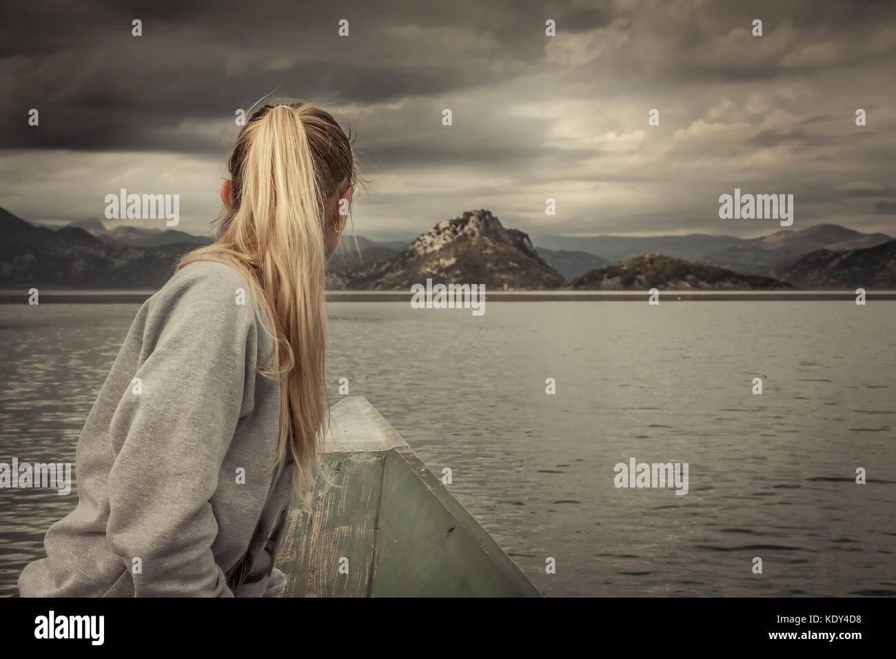 Frau traveler Segeln auf Boot in Richtung Ufer, mit Berge Landschaft am Horizont in bewölkten Tag mit dramatischen Stockbild