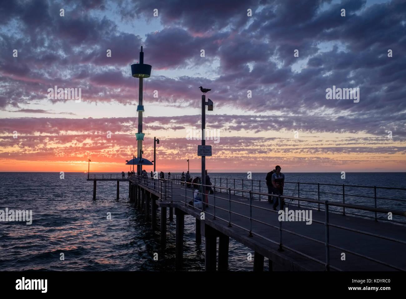 Die Menschen genießen einen wunderschönen Sonnenuntergang am Meer auf der Adelaide von Brighton Pier an Stockbild