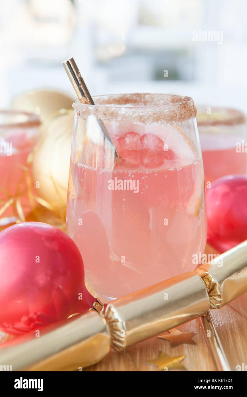 Rosa Sekt Cocktail und Festliche Weihnachtsdekorationen Stockbild