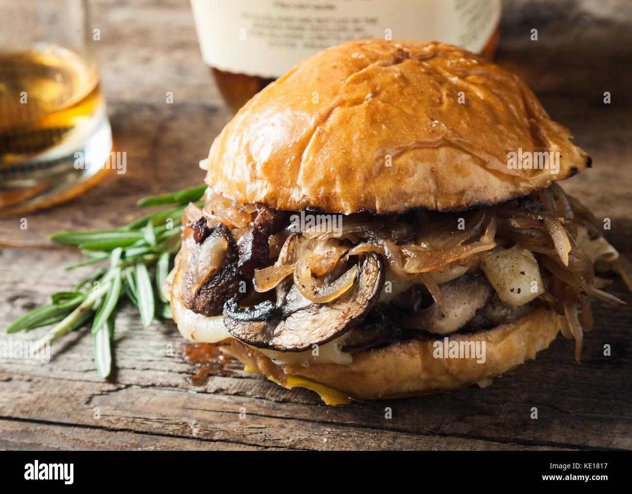 Burger mit Pilzen, gebratenen Zwiebeln und Käse auf rustikalen Hintergrund Stockbild