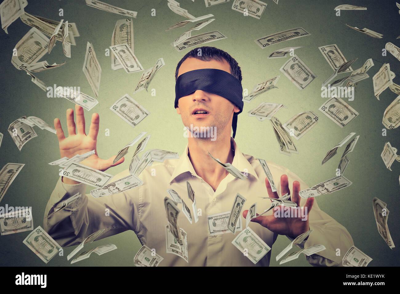 Mit verbundenen Augen junger Geschäftsmann versucht, Dollar, Rechnungen zu fangen Banknoten fliegen in der Stockbild