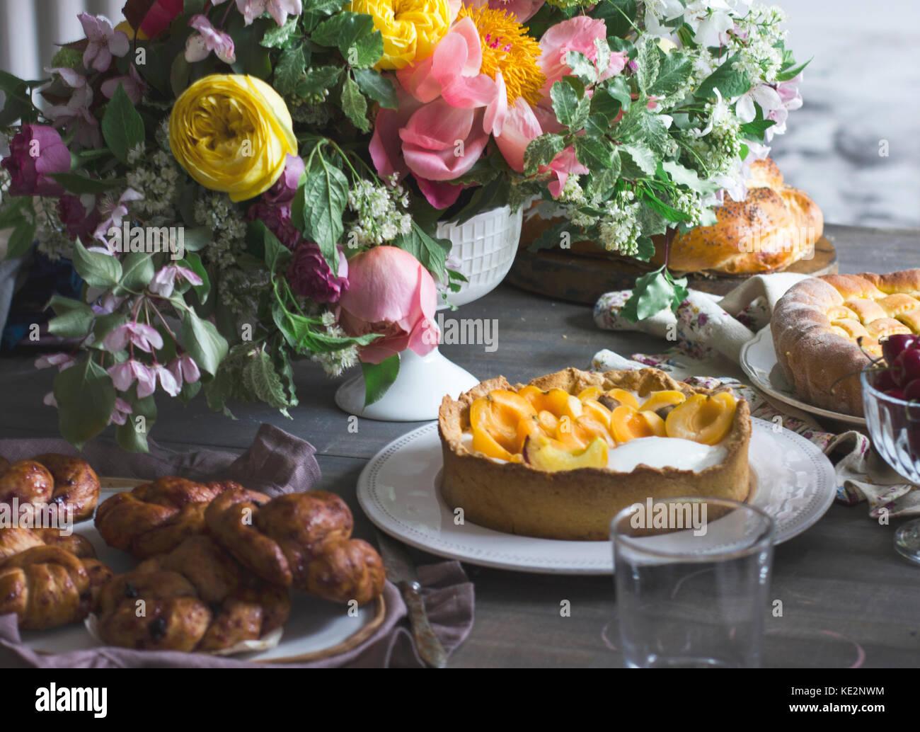 Festliche Tafel mit großen Blumenstrauß, hausgemachte Kuchen und Gebäck Stockbild