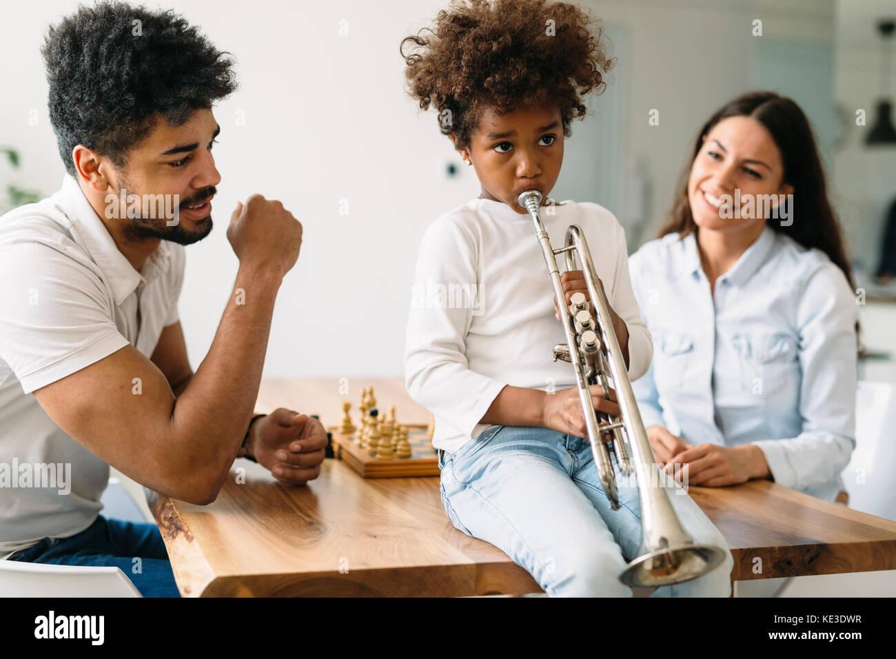 Stolze Eltern ihrem Kind beobachten Trompete spielt. Stockbild