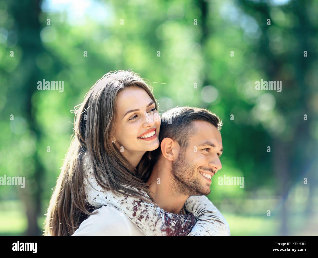 Paar Mann und Frau Spaß Huckepack im Park. Glücklich lächelnde Freund und Freundin genießen Stockbild