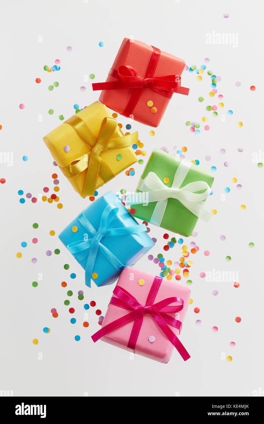 Bunte Geschenkboxen mit Konfetti fallen oder Fliegen in Bewegung. Stockbild