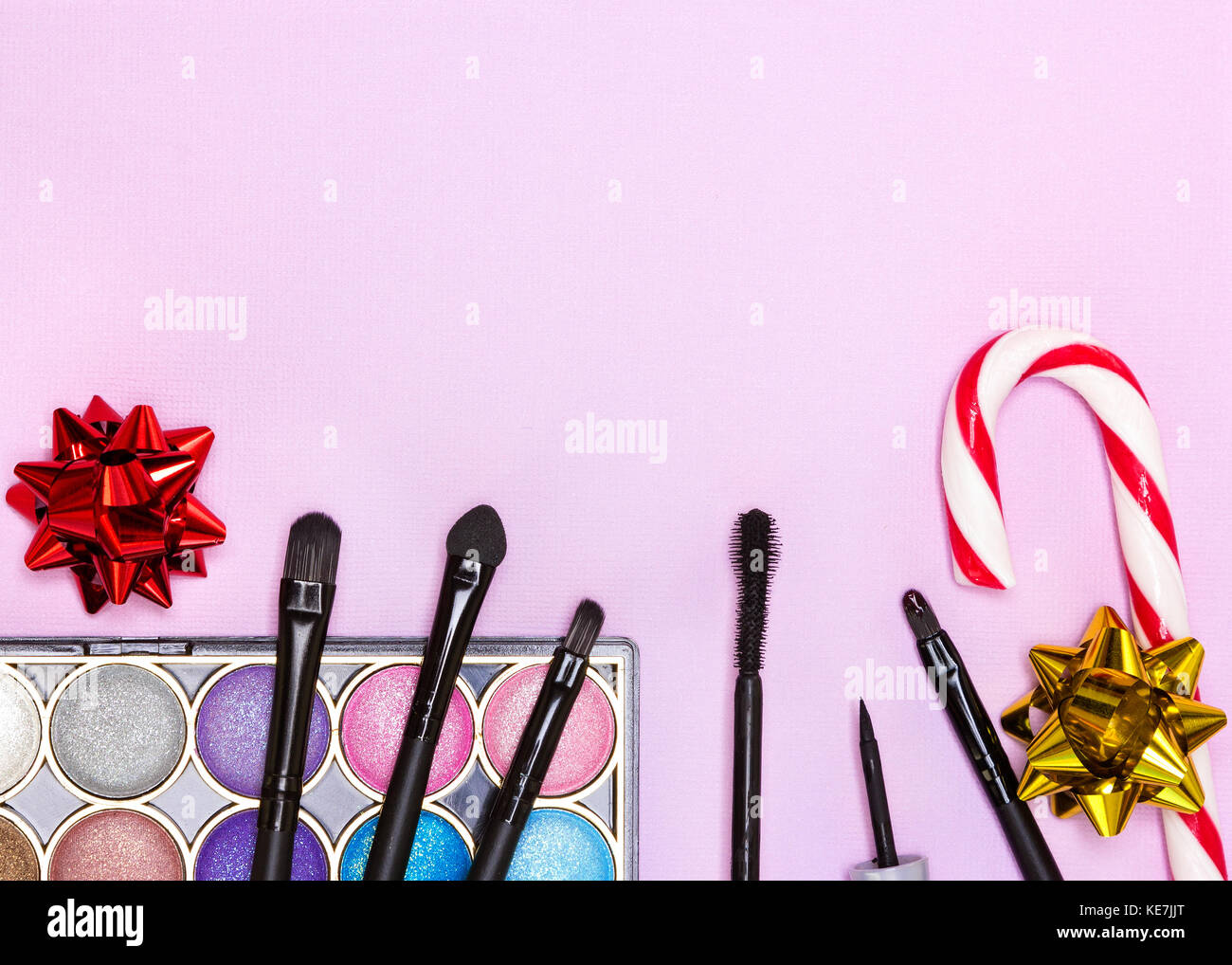 Weihnachten Make-up Kosmetik. Helle farbe Glitzer Lidschatten, schwarzer Eyeliner, Mascara, Lipgloss, Make up Pinsel Stockbild