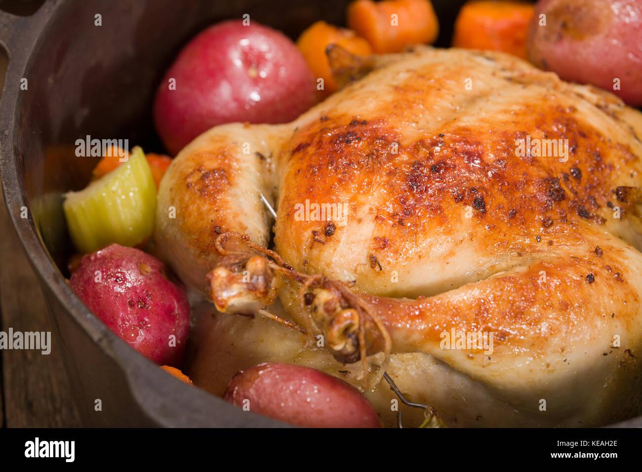 Im holländischen Stil gebratenes Huhn mit gebackenen rote Kartoffeln, Karotten und Sellerie, in einen gusseisernen Stockbild