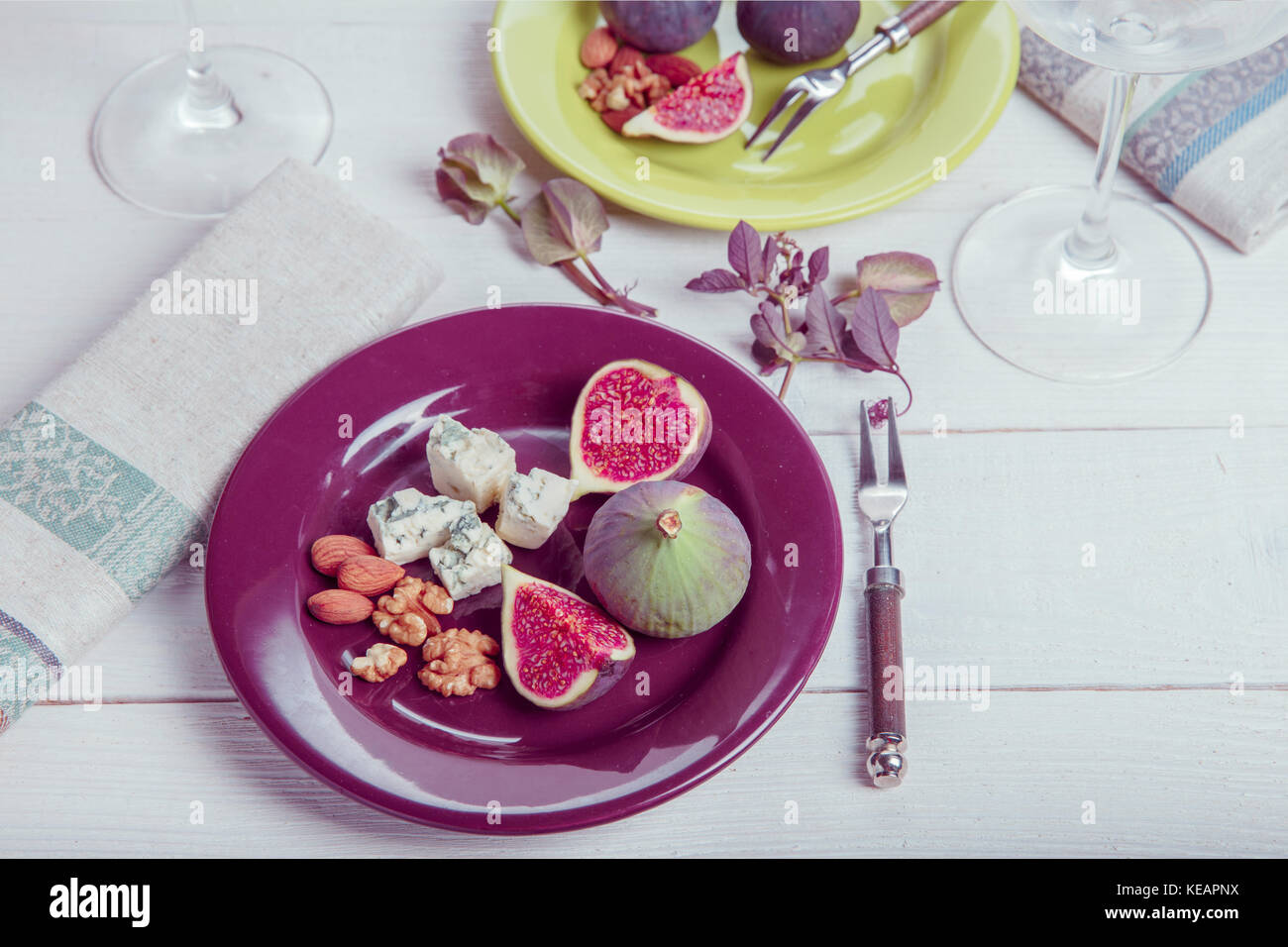 Mit der Tabelle, frische Feigen, Früchte, Beeren, Käse, Nüsse auf weißem Holz- Hintergrund Stockbild