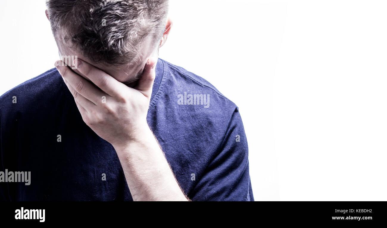 Mann mit der Hand im Gesicht auf weißem Hintergrund sich schämt Stockbild