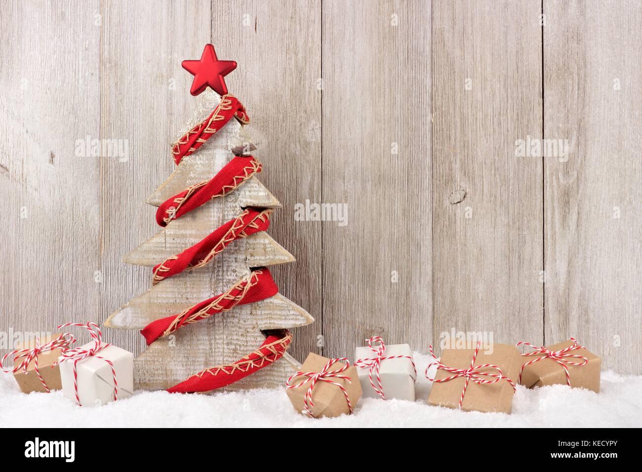 shabby chic holz weihnachtsbaum mit rustikalen red garland und geschenke im schnee vor einem. Black Bedroom Furniture Sets. Home Design Ideas