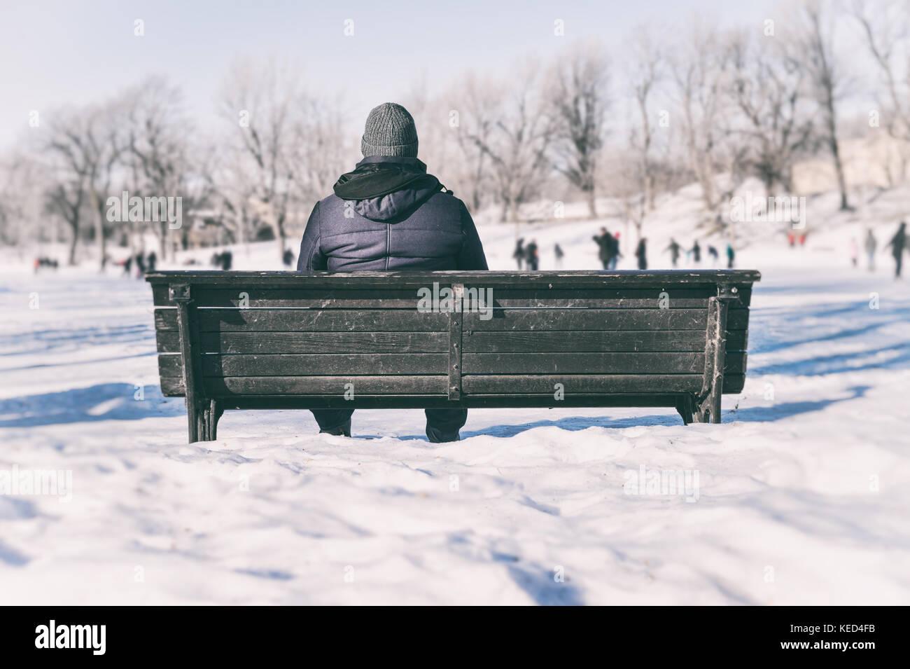 Mann sitzt auf der Bank mit Blick auf Leute Eislaufen Stockbild