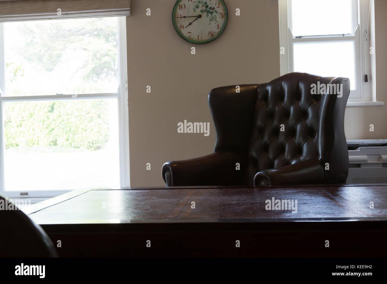 Uhr an der Wand hängend mit Sessel im Wohnzimmer zu Hause