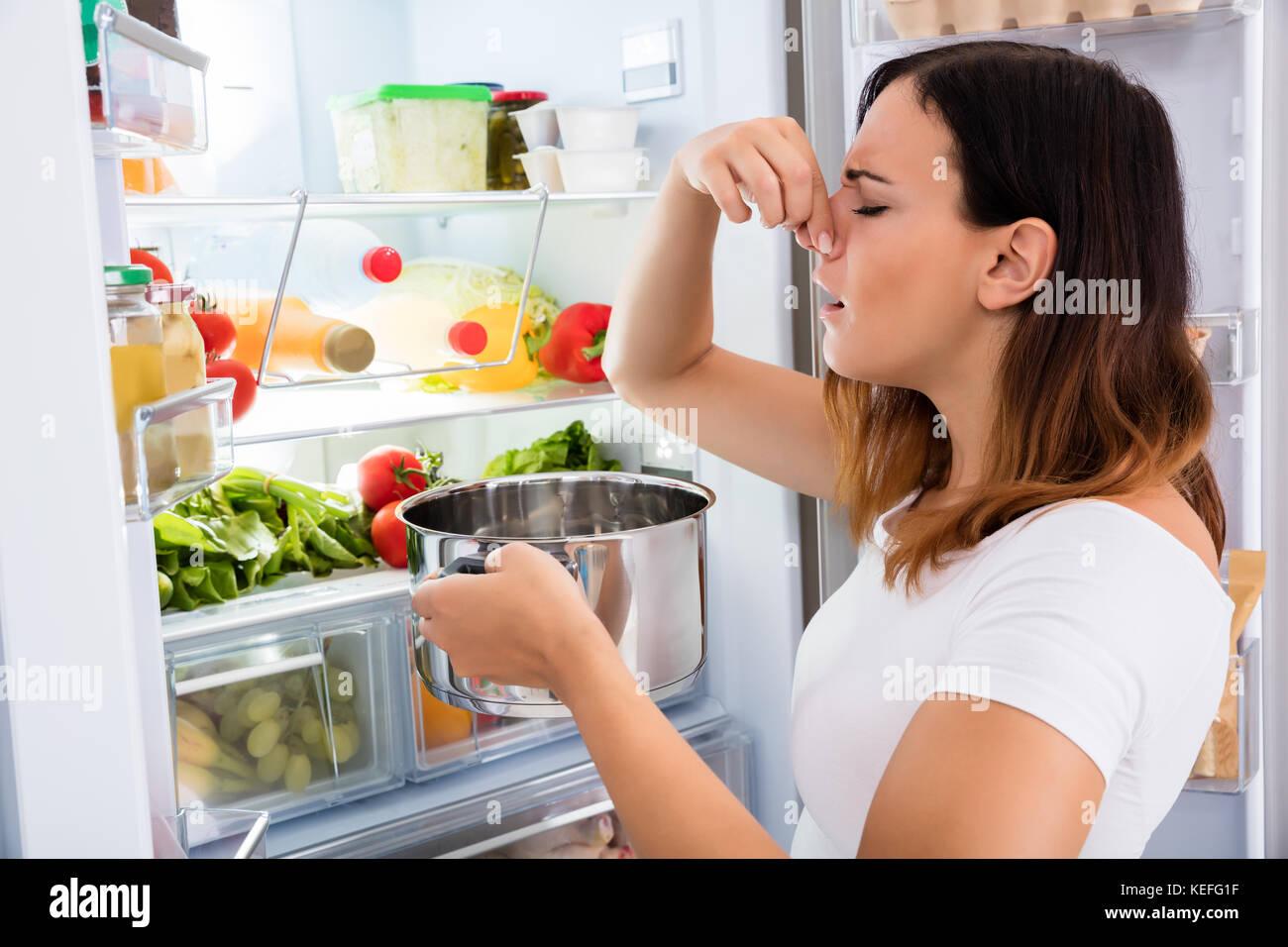Junge Frau bemerkt fauligen Geruch von Essen in der Nähe von offenen Kühlschrank Stockbild