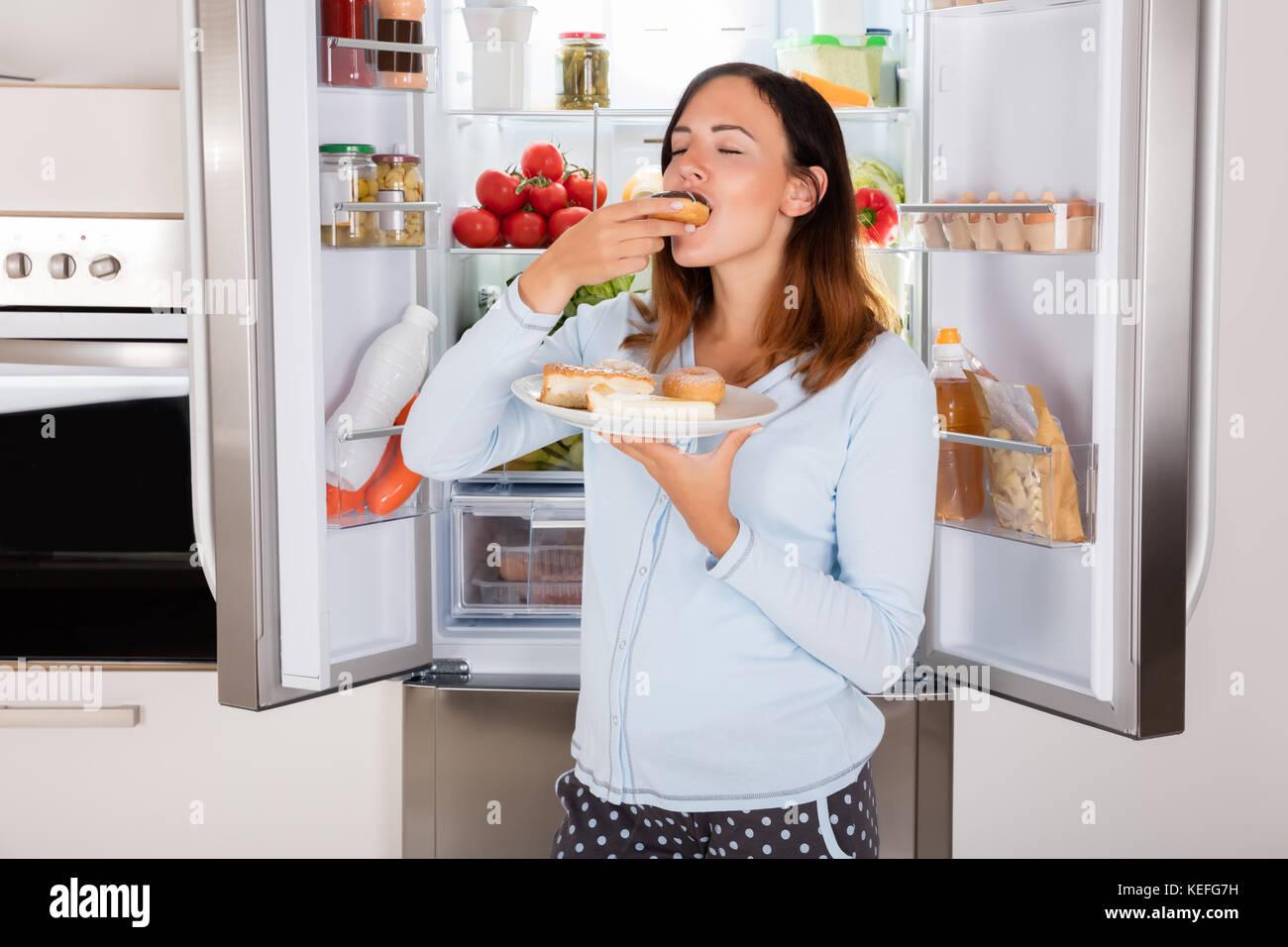Kühlschrank Platte : Junge frau genießen essen donut von der platte in der nähe der