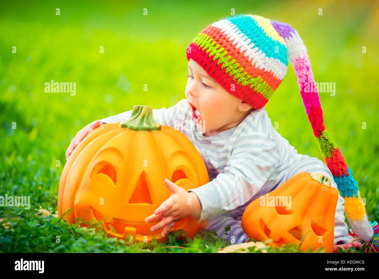 Süße kleine baby boy trug lustig bunte hat versucht zu beißen schöne geschnitzte festliche Kürbis, Stockbild