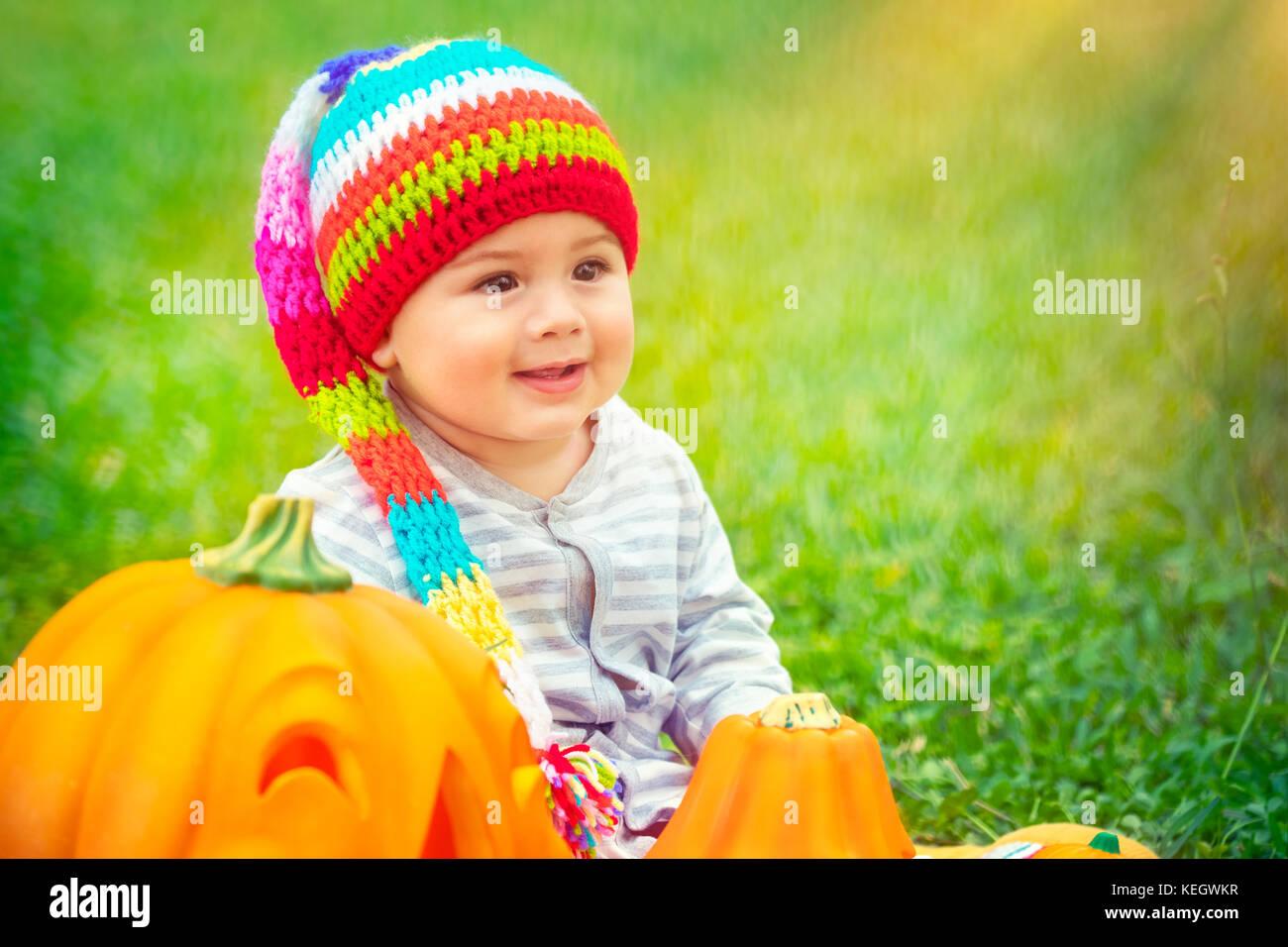 Kleines hübsches Kind sitzen auf der grünen Wiese in der Nähe von zwei süße Kürbisse Stockbild