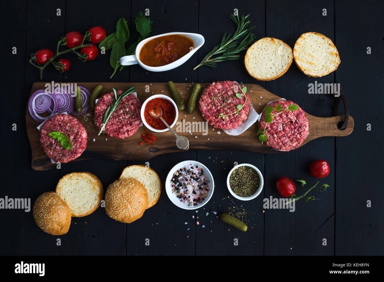 Zutaten zum Kochen Burger. rohes Hackfleisch Fleisch Schnitzel auf Holz Schneidebrett, roten Zwiebeln, Tomaten, Stockbild