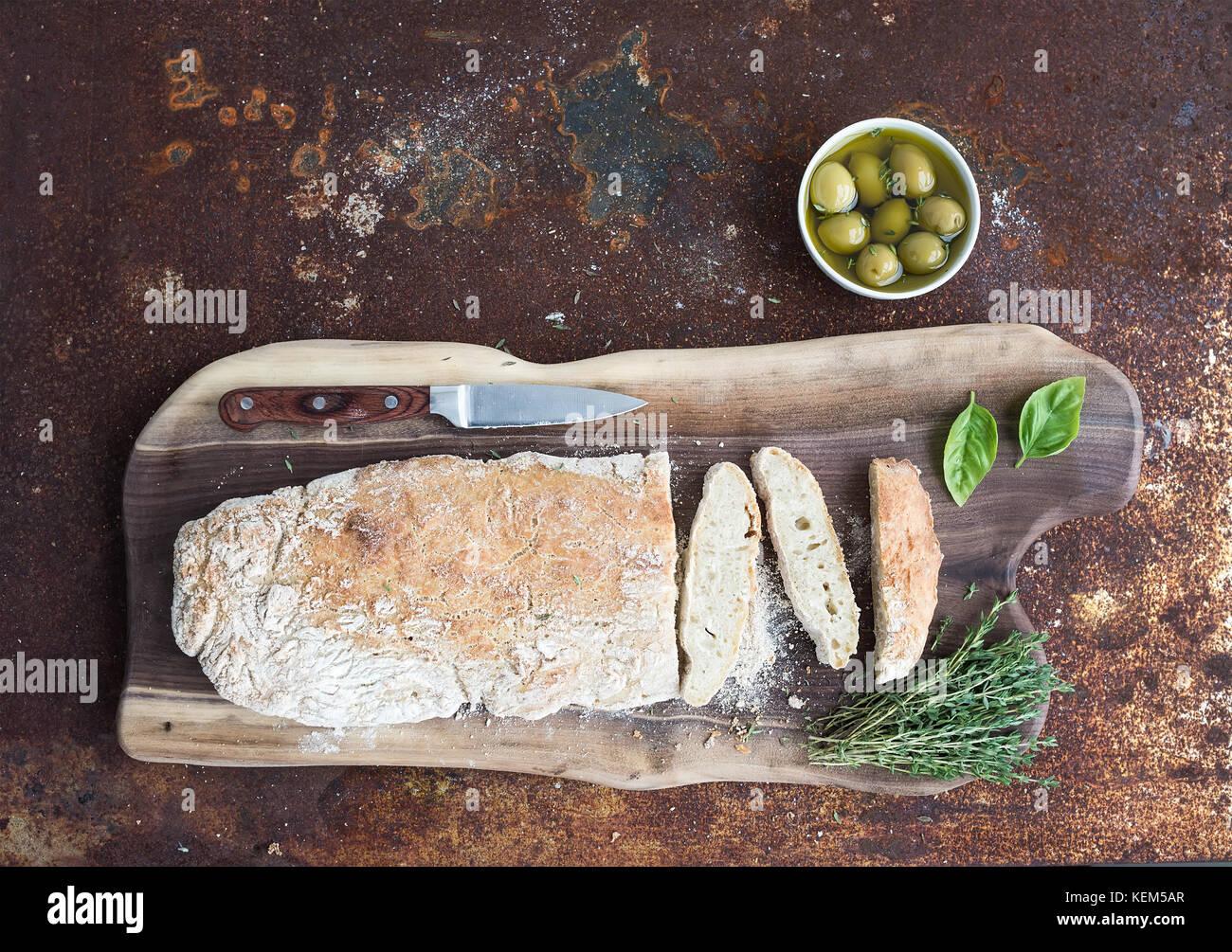 Frisch gebackene hausgemachten Ciabatta Brot mit Oliven, Basilikum und Thymian auf Nussbaum Holz Brett über Stockbild