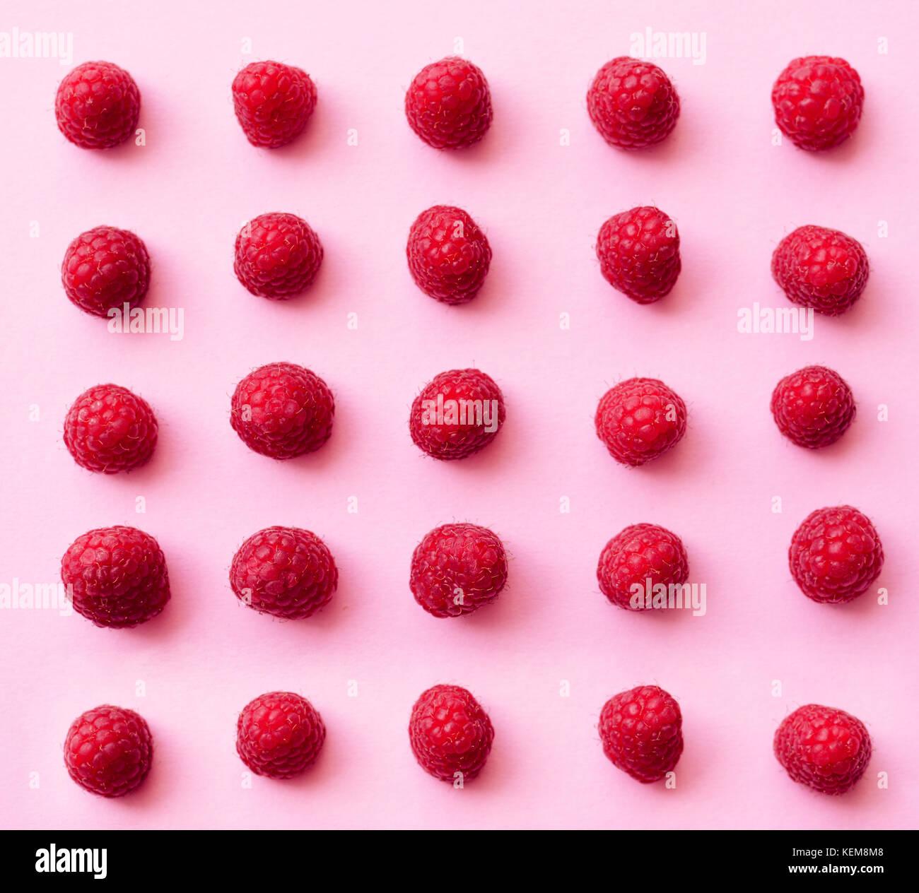 Eine schöne Auswahl an frisch gepflückte reife rote Himbeeren am trendigen rosa Hintergrund. Farbenfrohe Stockbild
