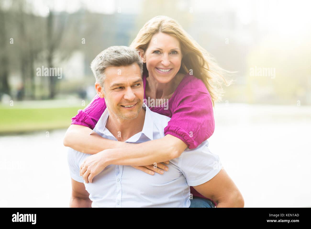 Portrait von glücklichen Mann huckepack seine Frau Stockbild