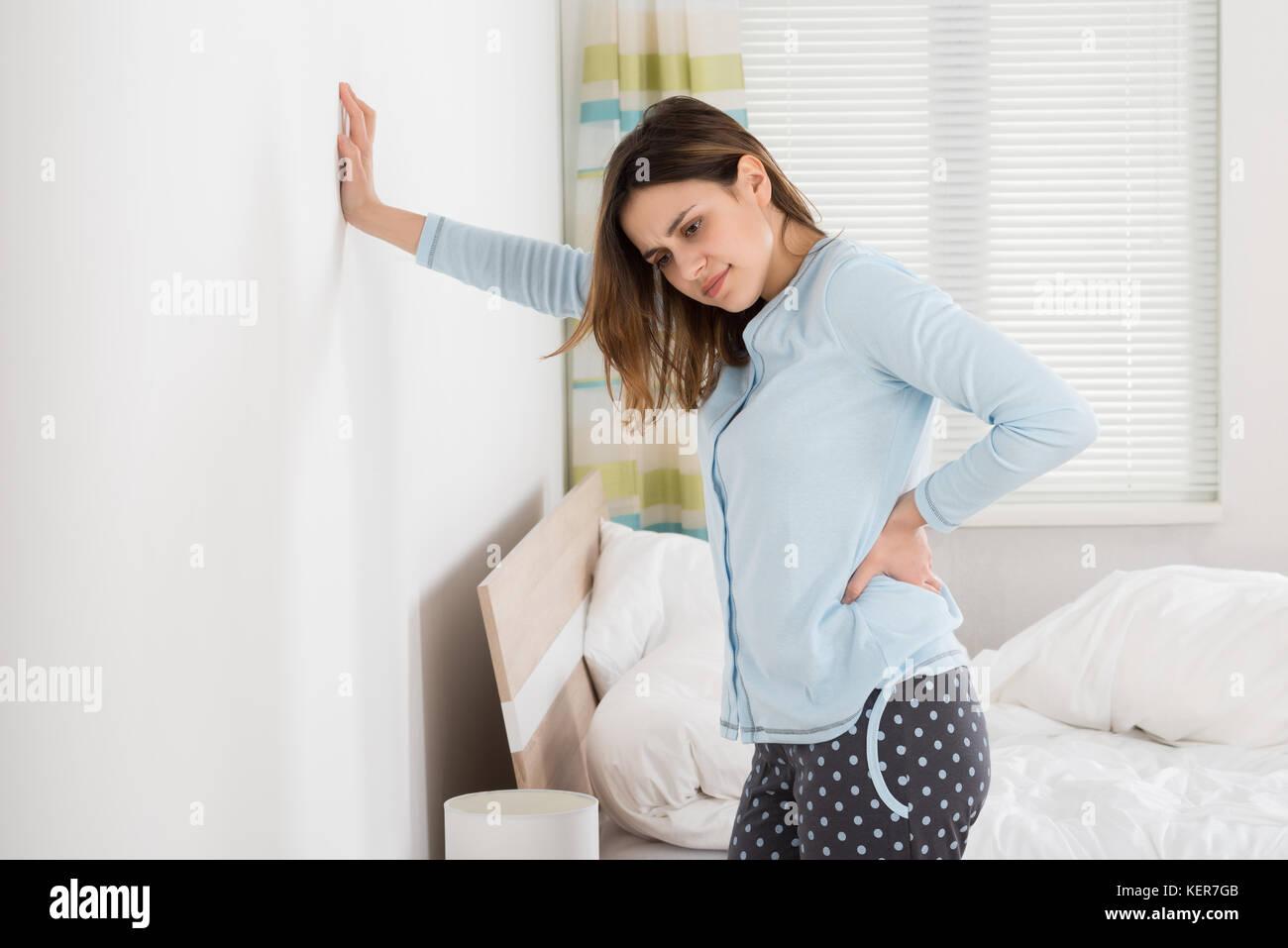 Frau leiden unter Rückenschmerzen, gegen Wand Stockbild