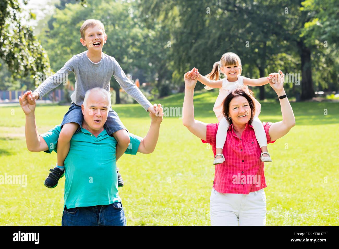 Glückliche Familie Spaß mit Kinder piggyback Ride in Park Stockfoto