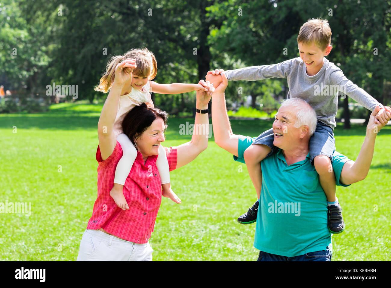 Gerne ältere Großeltern genießen Spaß piggyback Ride mit Kindern zusammen in Park Stockbild