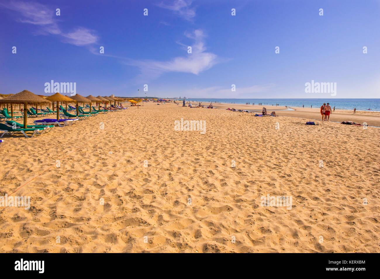 Weitläufige Sandstrand von Manta Rota Algarve Aussaat strohgedeckten Sonnenschirmen und Strandliegen. Stockbild