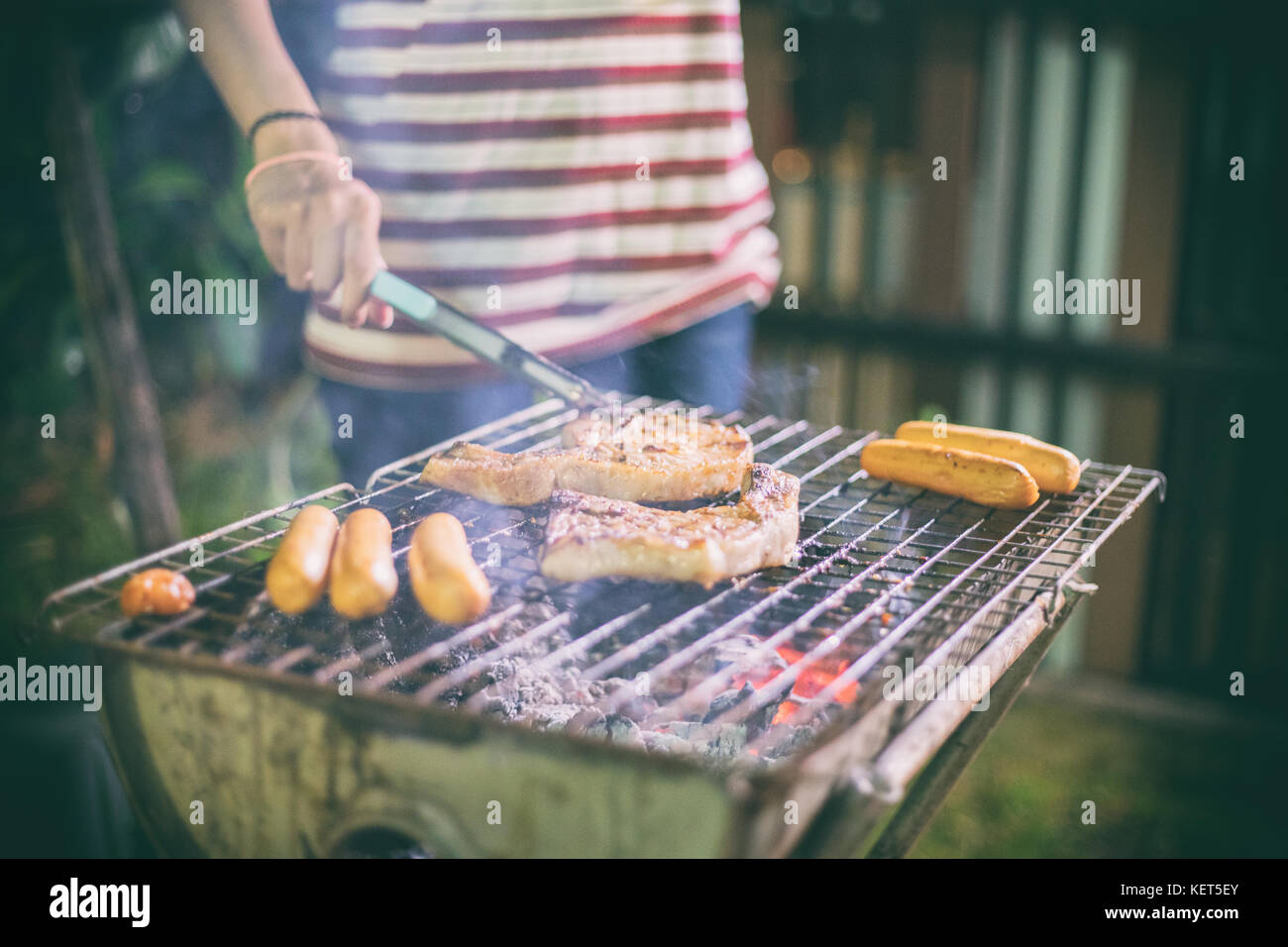 Asiatische Gruppe von Freunden, Grill und gegrillten shashliks auf das Gitter Party im Garten Stockbild