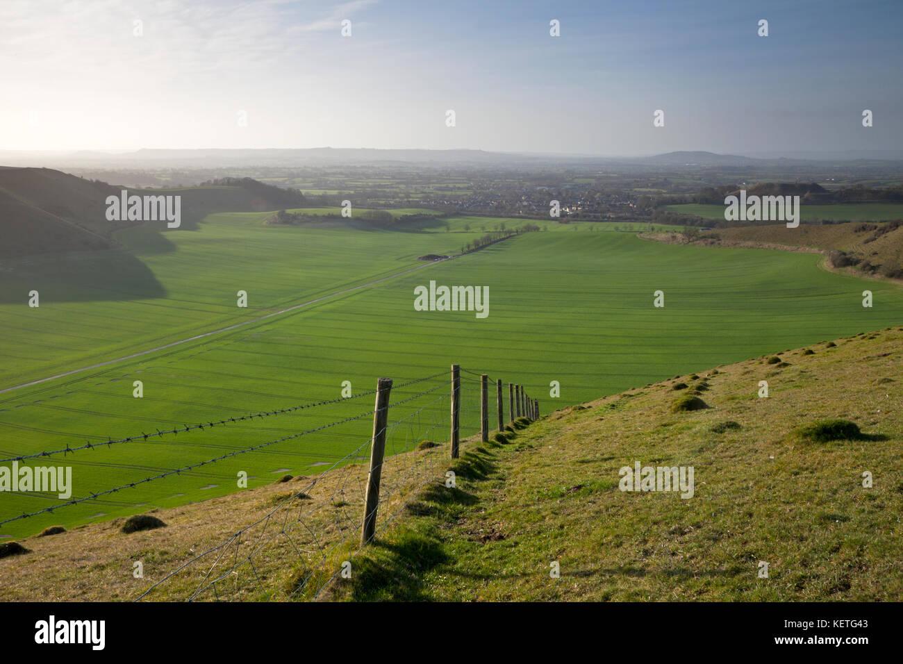 Ein stacheldrahtzaun auf stark geneigten Chalk downland in der Nähe von Reine in Wiltshire. Stockbild