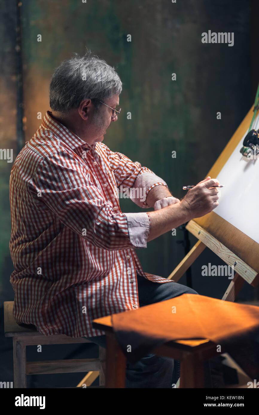 Die ausgereifte kreative Techniker arbeiten mit Projekt am Reißbrett Stockbild