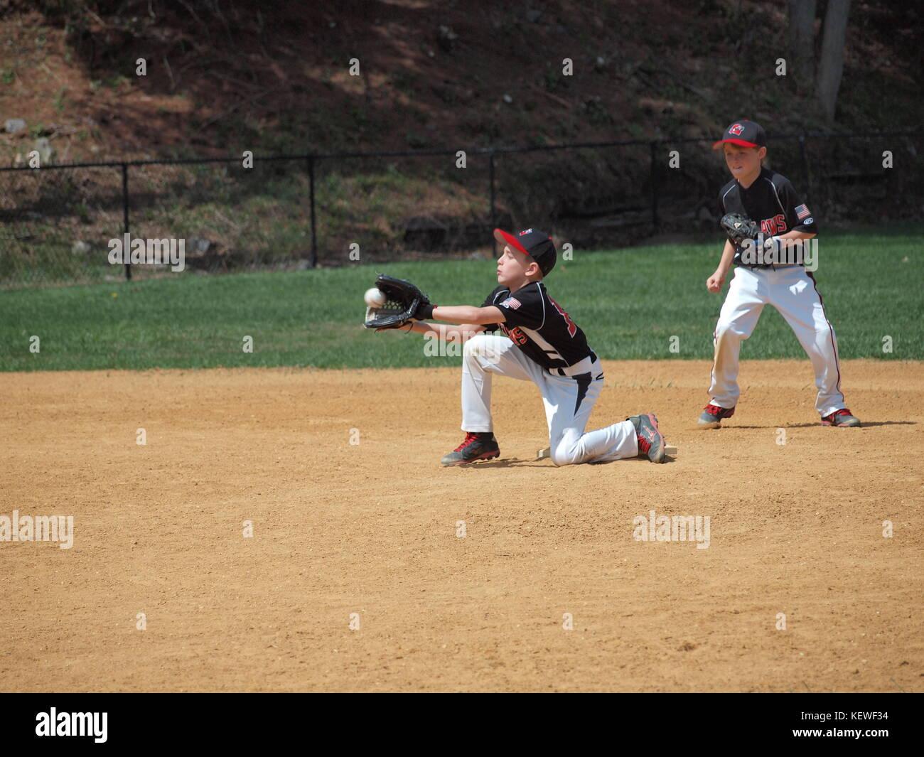 Der kleine Liga-Feldspieler stoppt den Ball am heißen Sommertag. Stockfoto