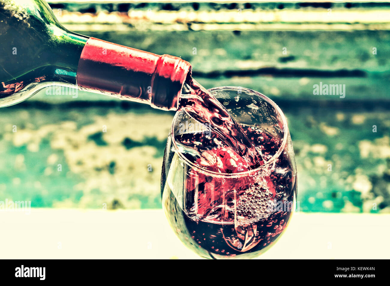 Weihnachten, Neujahr. Gießen rot Wein. Wein in ein Glas. selektive Fokus, Bewegungsunschärfe, Rotwein in ein Glas. Stockfoto