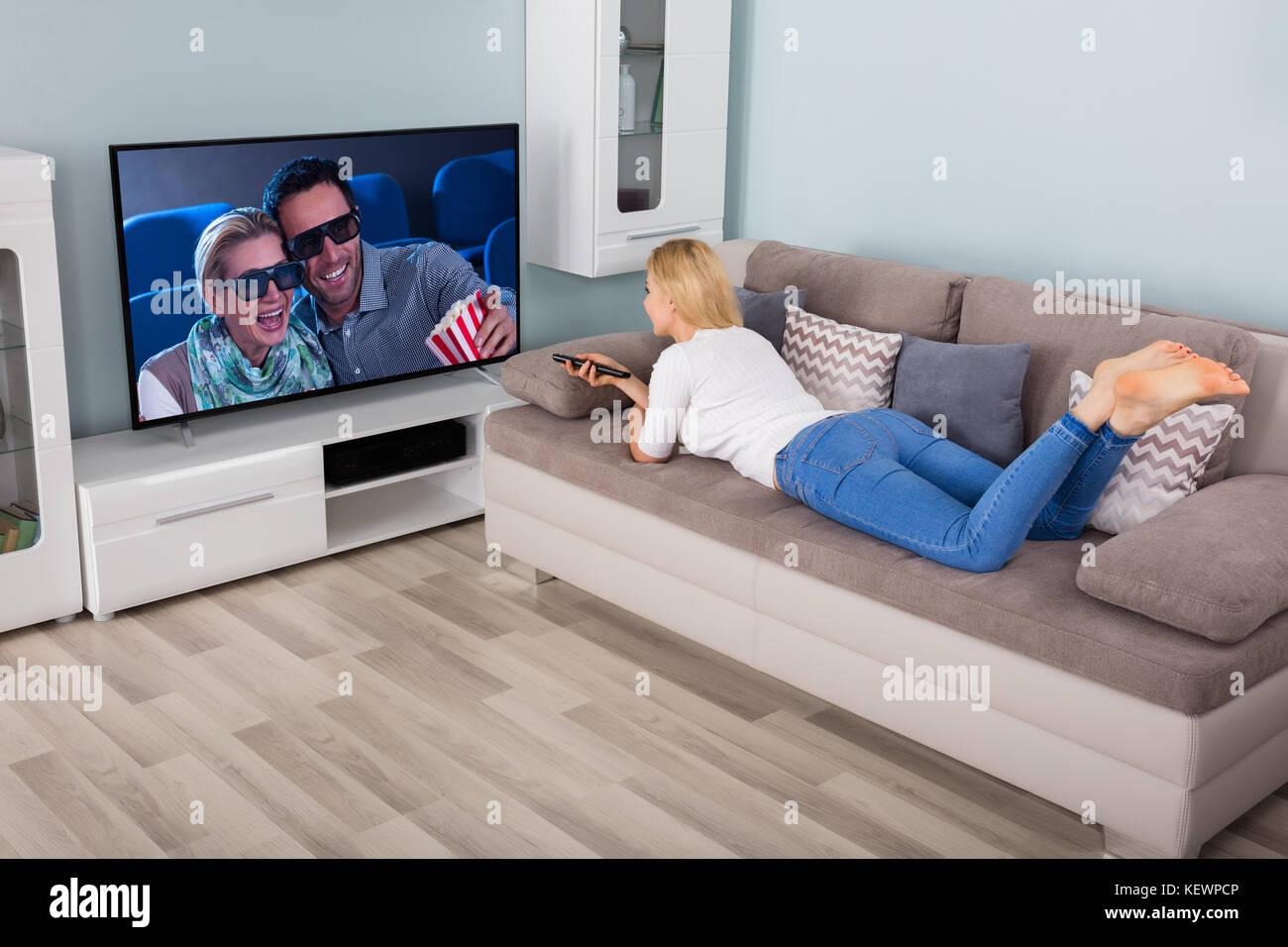 Liegende Frau Auf Der Couch Watching Film Auf Dem Fernseher Im