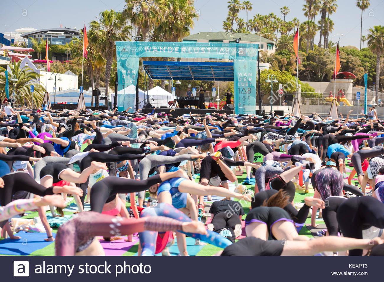 Leute, die eine Beinen nach unten schauender Hund Pose während outdoor Yoga Festival am Santa Monica Pier in Stockbild