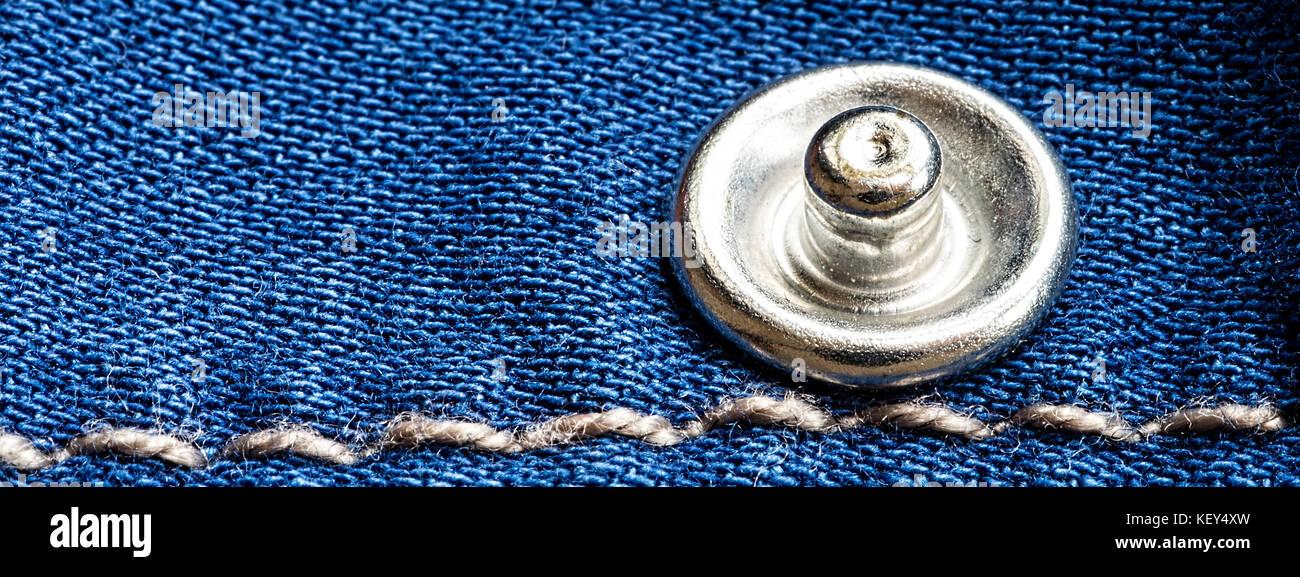 Jeans-Textur mit Nieten und Faden hautnah. Blue Denim Stoff Hintergrund. Stockbild