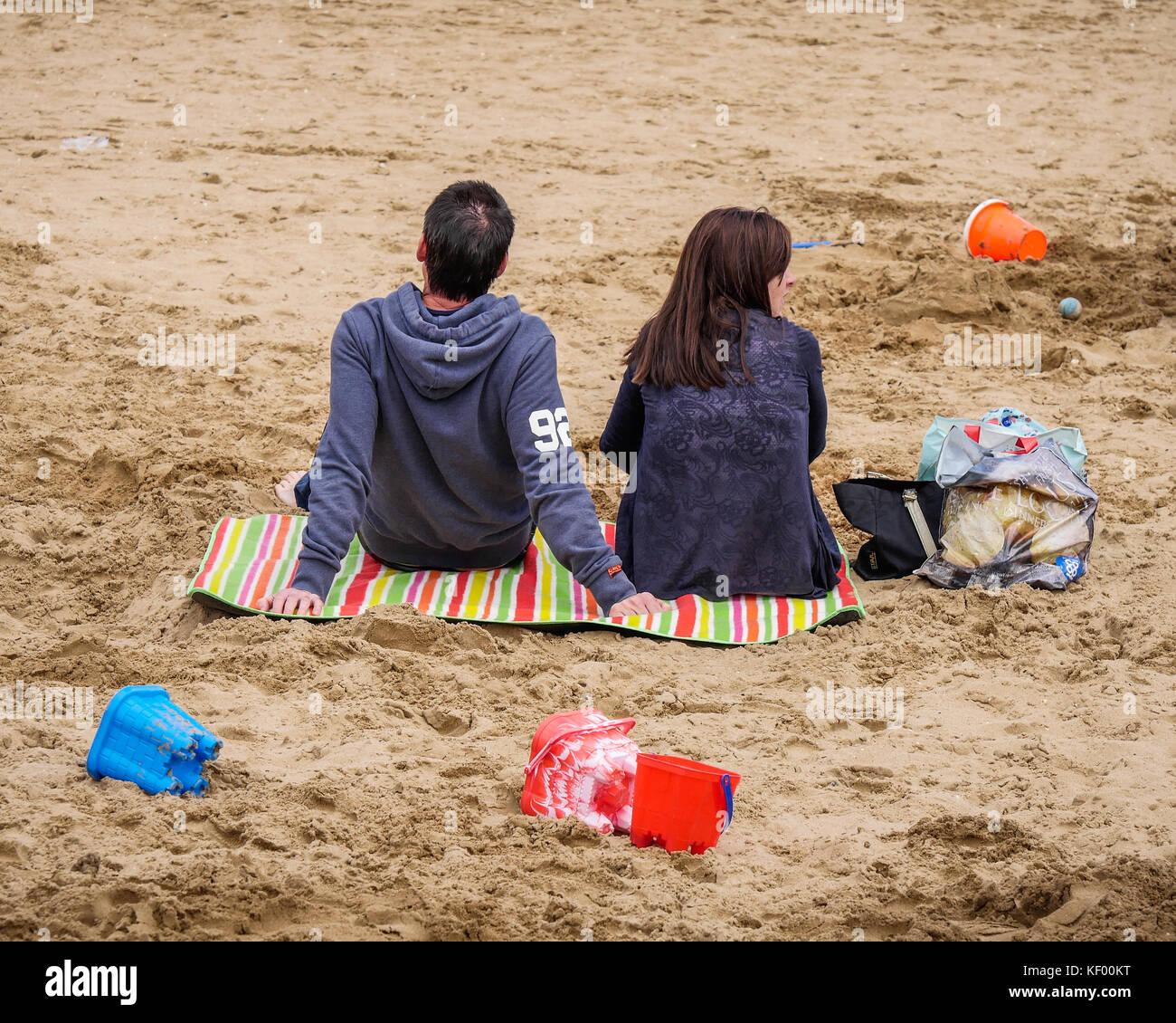 Ein Paar auf einem Meer Strand sitzen Stockbild