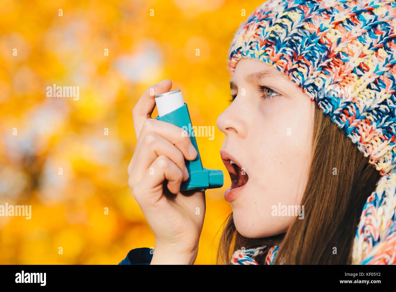 Junges Mädchen mit Asthma Inhalator in einem Park - chronische Krankheit, Allergie Remedy verursachtes Asthma Stockbild