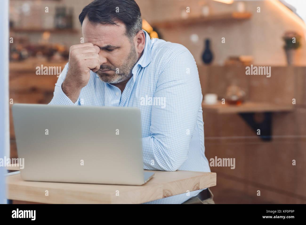 Deprimiert Geschäftsmann mit Laptop Stockbild
