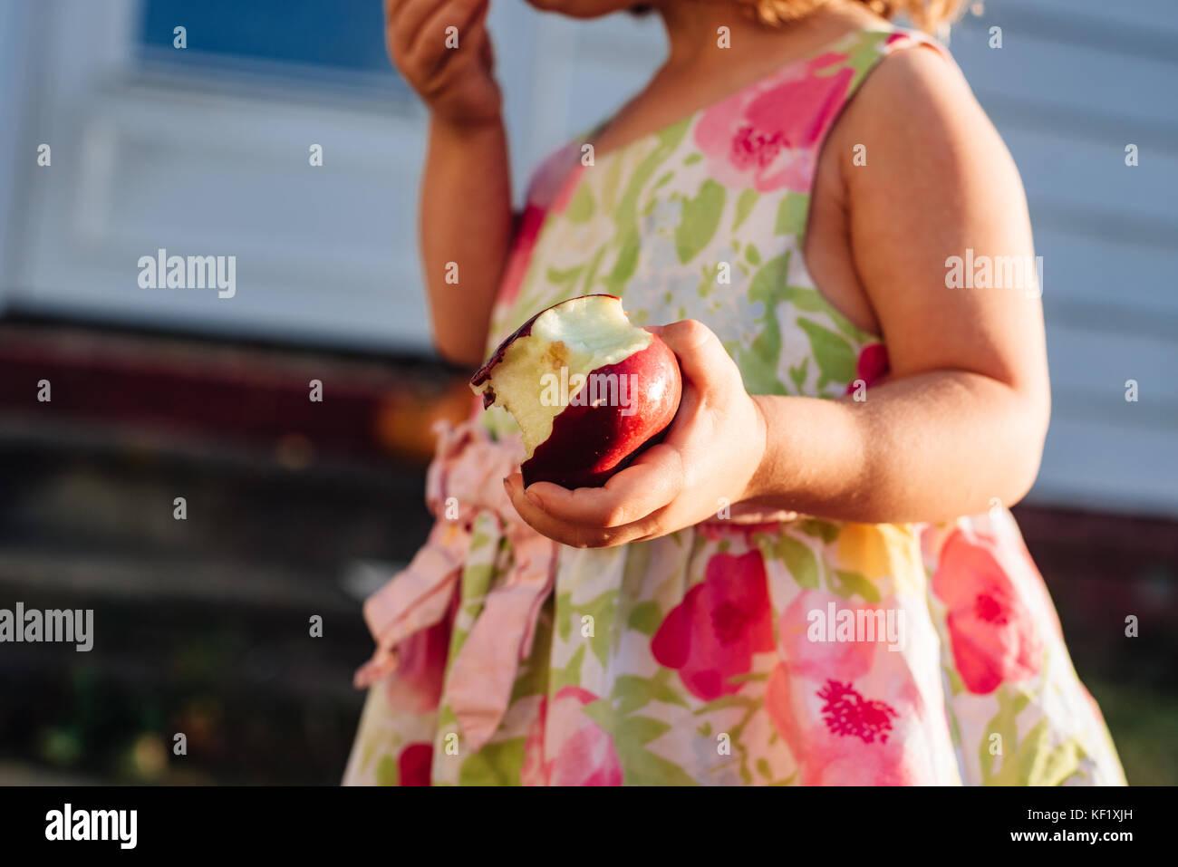 2-3 Jahre alten Holding halben Apfel gegessen. Stockbild
