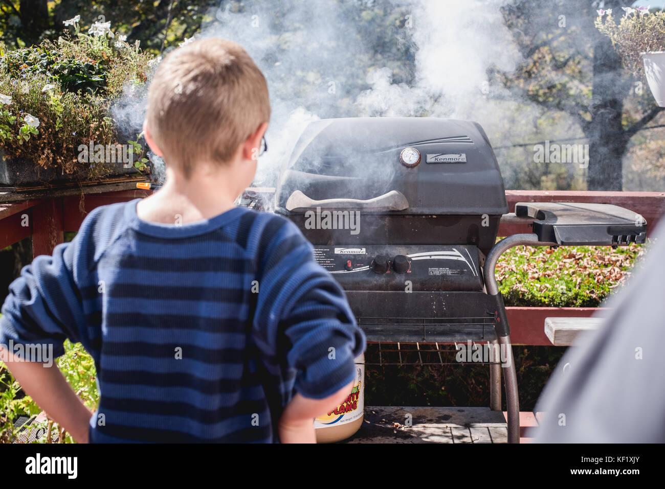 10-jähriger Junge auf der Suche nach Grill mit Rauch Stockbild
